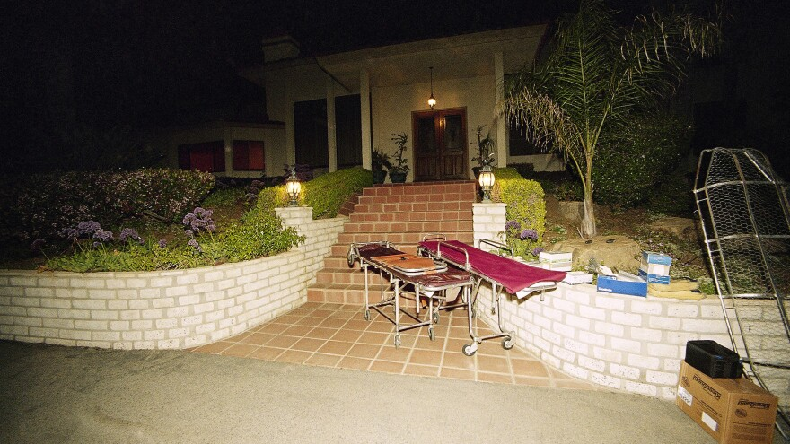 Gurneys are shown in front of the Southern California mansion where, in 1997, members of the Heaven's Gate cult killed themselves by ingesting poison.