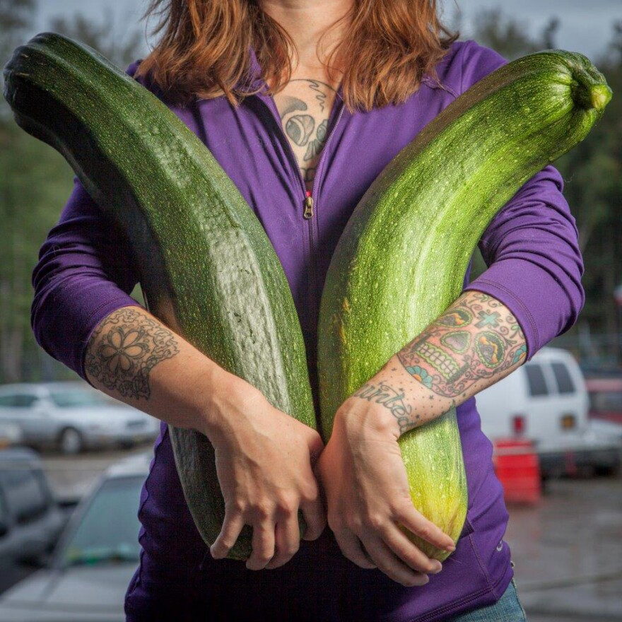 """Alaska grower Brittney Kauffman holds two zucchinis she entered in a giant vegetable competition in 2013. """"Alaska is just a hotbed for gardening, believe it or not,"""" says Alaska State Fair crops superintendent Kathy Liska. """"Everybody thinks that we're always under ice — no!"""""""