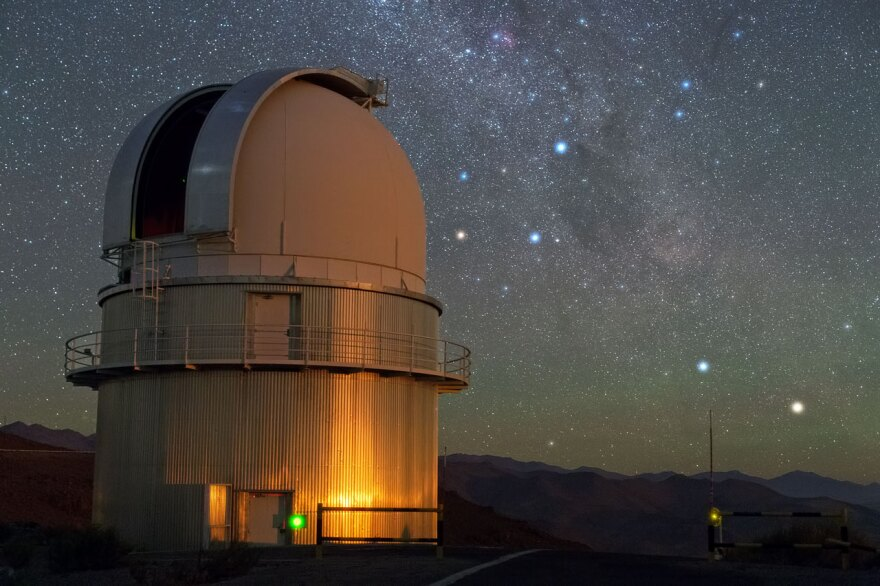 In the sky above ESO's La Silla Observatory, the Southern Cross is visible to the right of the dome of a Danish 1.54-metre telescope. To the lower right of the image, two stars sparkle in the dark sky. From right to left, these are Alpha and Beta Centauri. Alpha Centauri is a multiple star, the nearest star system to Earth. A little closer to Earth than the bright components of Alpha Centauri, and invisible to the naked eye, is Proxima Centauri, the third star belonging to this multiple star system. (European Southern Observatory/Flickr)