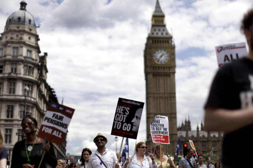 People march past the Houses of Parliament with placards as they take part in a protest to mark the nationwide day of strikes in London.