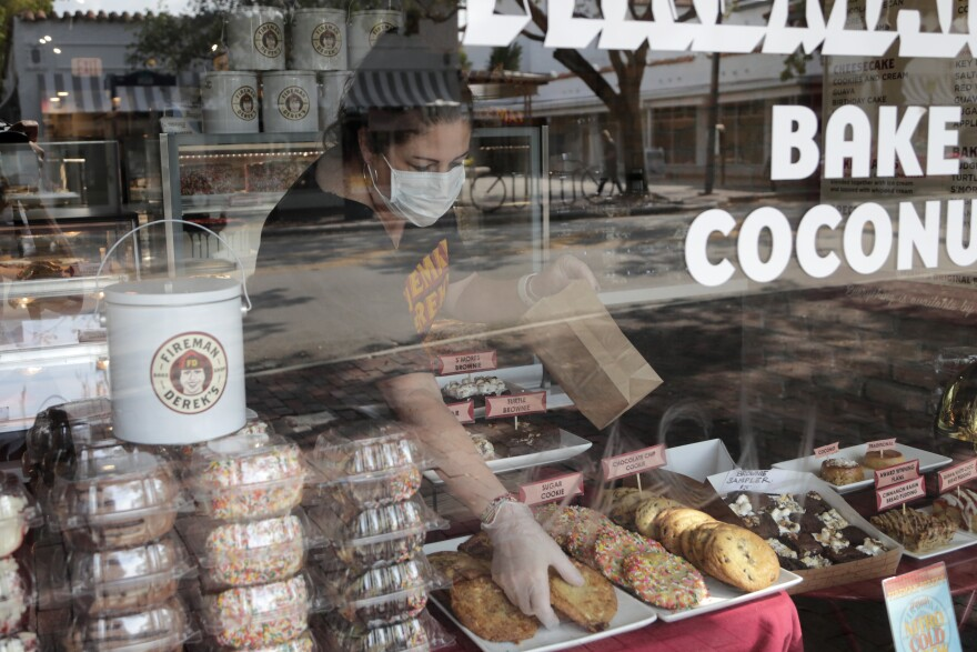 Tam Rubin, co-owner of Fireman Derek's Bake Shop, wears a protective mask and gloves as she fills a customer's order during the new coronavirus pandemic, Thursday, April 9, 2020, in Miami. The bake shop is open for take out only and and has not yet had to reduce staff due to the virus outbreak. (AP Photo/Lynne Sladky)