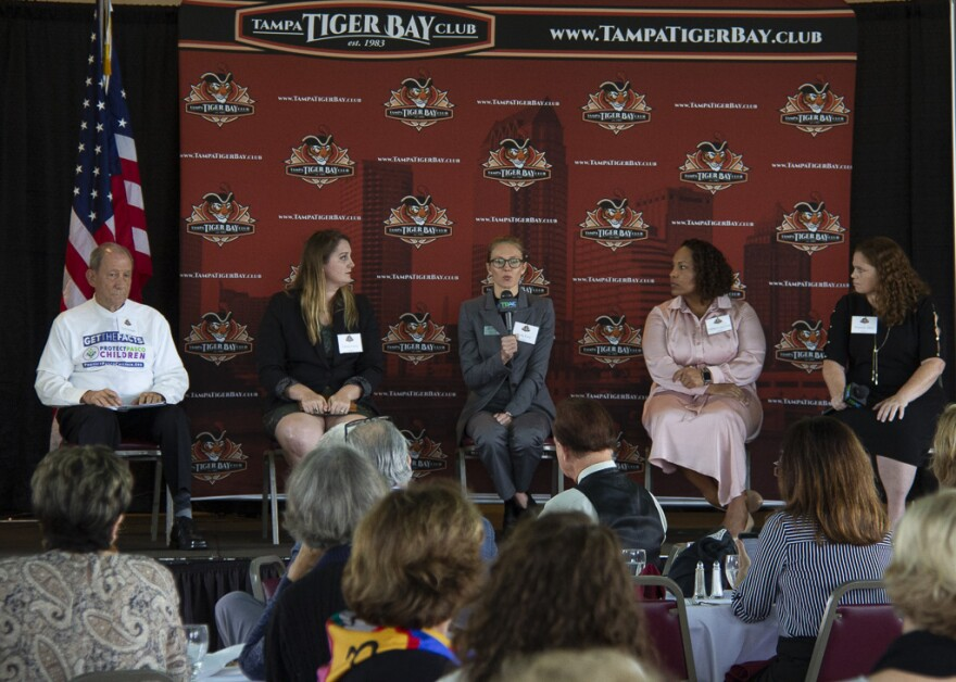 Five panelists discuss on stage at the Tampa Tiger Bay Club meeting in Ybor City.