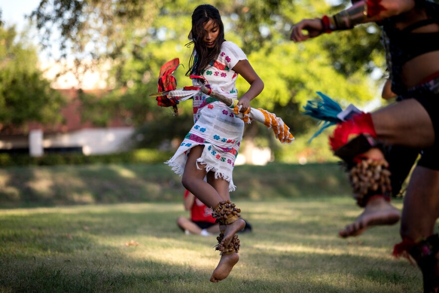 Katya Guzman takes part in a ceremonial dance last week in front of UT's J.J. Pickle Research Campus. The Miakan-Garza Band in San Marcos believe centuries old remains held by the archeological research lab are their ancestors.