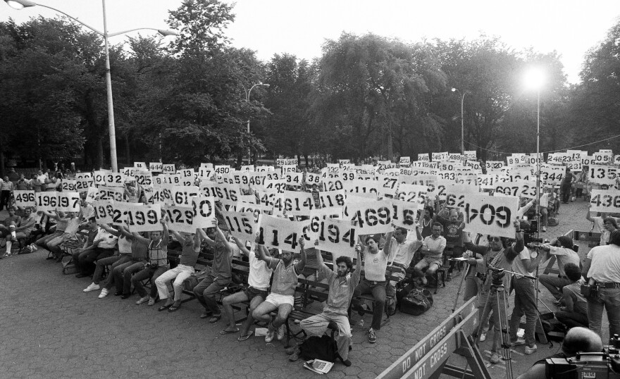 Cards representing AIDS victims are held aloft during a 1983 interdenominational service in New York's Central Park.