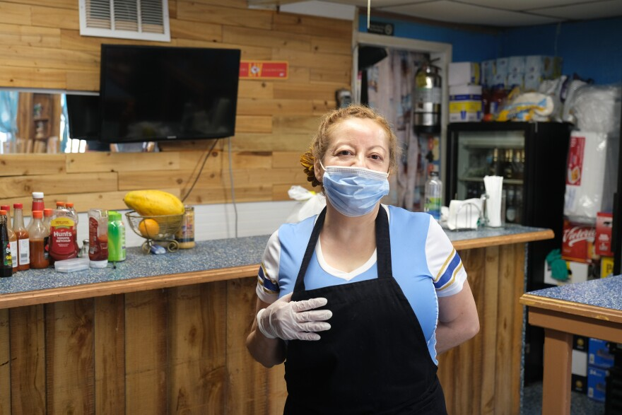 Picture of a woman in a black apron and wearing a blue face mask standing in a restaurant