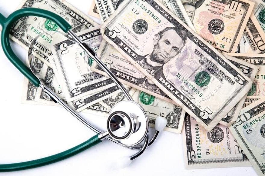 Stethoscope on a pile of dollars.