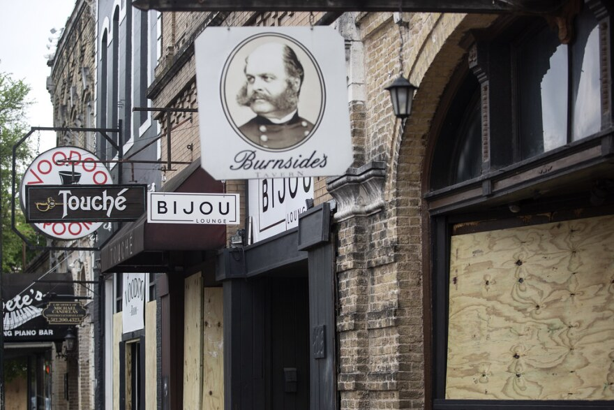 Bars and businesses are closed and boarded up on Sixth Street on Thursday.