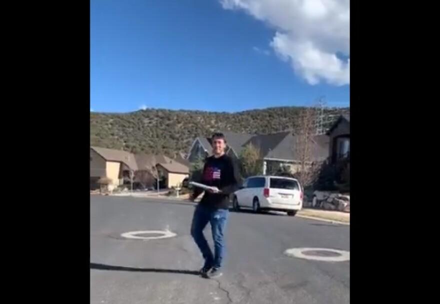 Man wearing a black t-shirt walking across a residential street carrying a clipboard