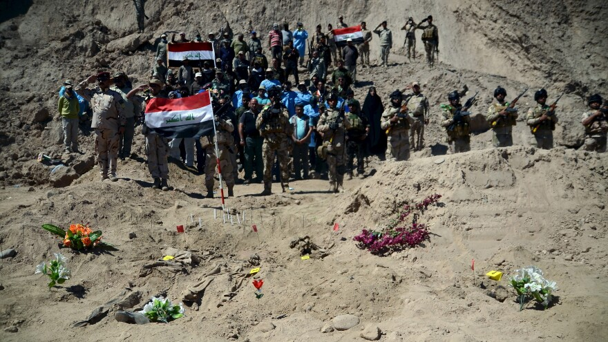Iraqi soldiers salute as they stand next to a mass grave believed to hold Shiite soldiers from Camp Speicher who were killed by Islamic State militants.