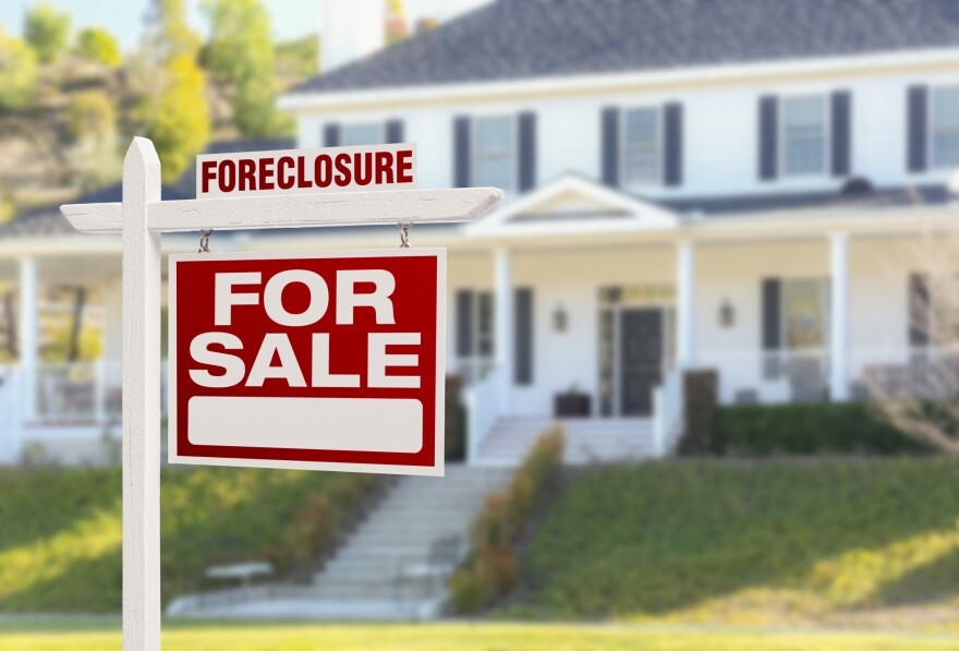 A fore sale foreclosure sign sits in front of a house.