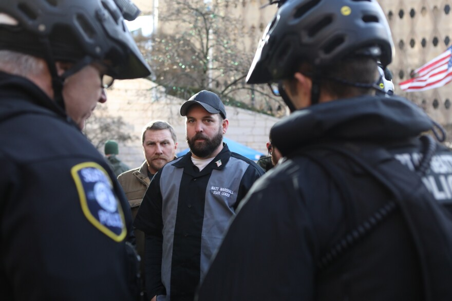 Matt Marshall, state leader of the Washington Three Percent, talks with law enforcement during the rally. He is trying to distance his group from the militia image.
