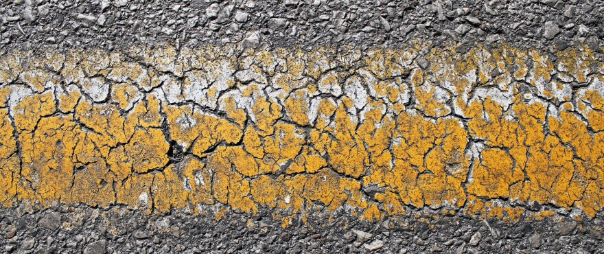 Horizontal photo of a cracked and fading yellow road stripe in St. Louis.
