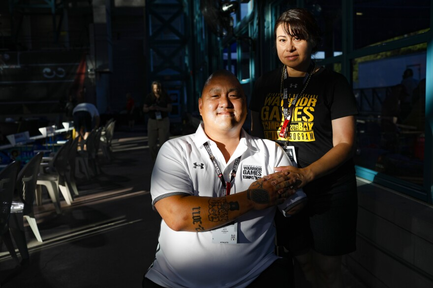 Retired Staff Sgt. Matt Lammers holds the hand of his wife, Alicia, before the swimming competition at the 2019 Department of Defense Warrior Games in Clearwater, Fla. Alicia has been Matt's official caregiver for nearly eight years, but she was cut from the Department of Veterans Affairs' caregiver program last December.