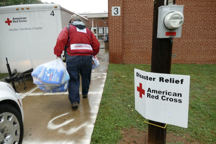 A Red Cross worker carries supplies to an emergency shelter at East Mecklenburg High School. The shelter has been filling up with people evacuating from the coast, and locals without a safe place to ride out the storm.