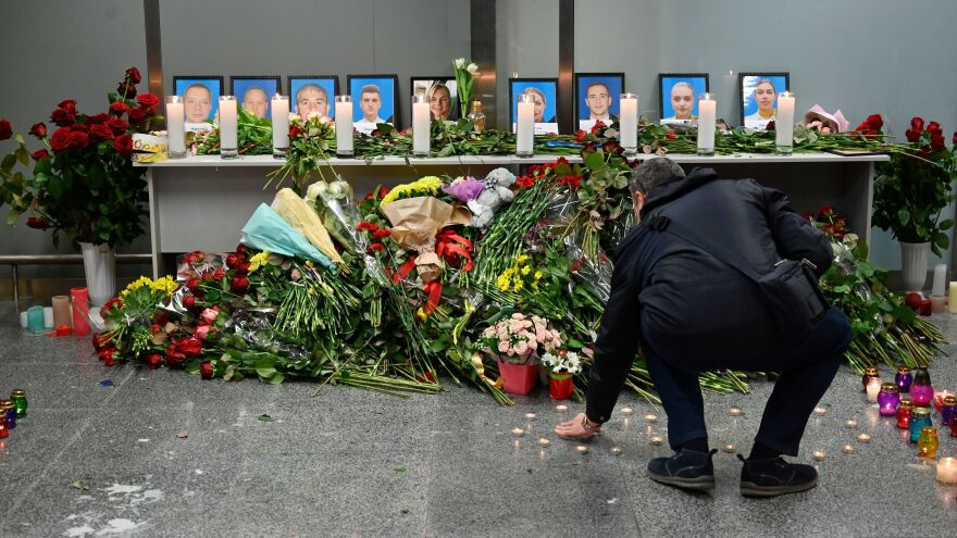 A man contributes to a memorial for the crash victims set up Wednesday at the airport outside Ukraine's capital, Kyiv. Among the 176 victims aboard the plane were 82 Iranians, 63 Canadians and 11 Ukrainians.