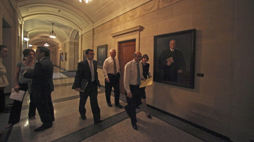 Joseph Cassioppi, David Lillehaug, Solicitor General Alan Gilbert and Attorney General Lori Swanson enter a hearing room before testimony Tuesday at a hearing at the Minnesota Capitol in St. Paul.    The hearing focused on services that will receive emergency funding while a state budget impasse continues.