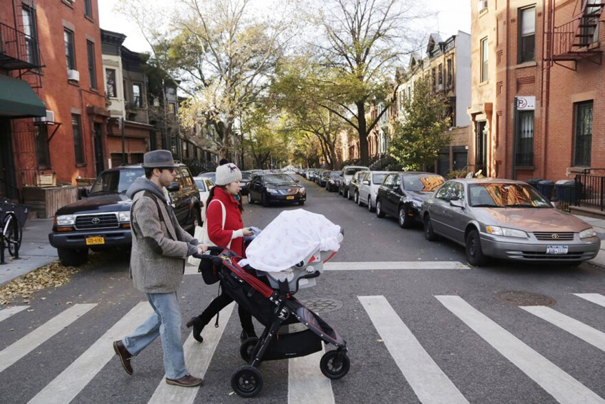 FILE - In this Nov. 14, 2013 file photo, a couple with a baby stroller cross the street in the Park Slope neighborhood in the Brooklyn borough of New  York. The rise in popularity of Brooklyn as a name for girls parallels the borough's renaissance through the gentrification of neighborhoods, an influx of tech firms, the construction of the Barclays Center as an entertainment hub and the relocation and rebranding of the New Jersey Nets basketball team. (AP Photo/Mark Lennihan, FILE)