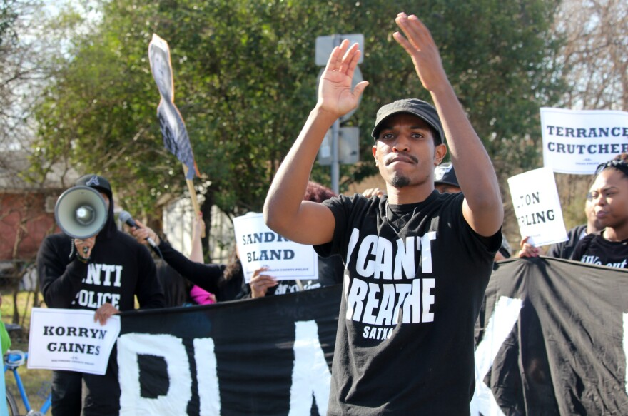 A Black Lives Matter activist leads a chant as protesters holding a banner block much of the road during the MLK Day march Jan. 15, 2018.