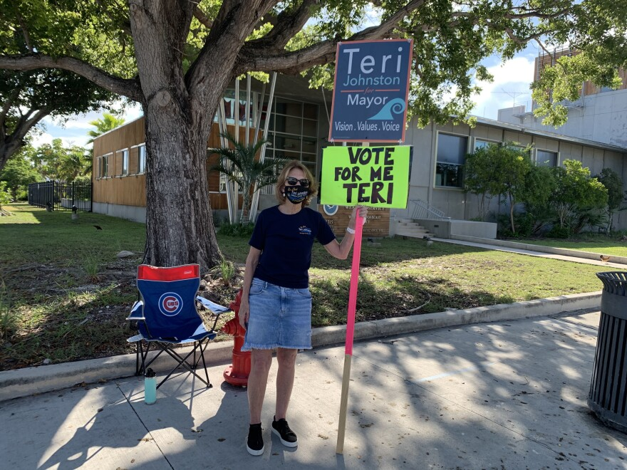 The photo shows Key West Mayor Teri Johnston holding a sign across the street from City Hall Tuesday.