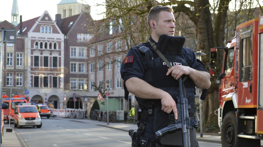 A police officer stands near the scene where a car crashed into a group of people in Muenster, Germany, leaving two dead, before killing himself.