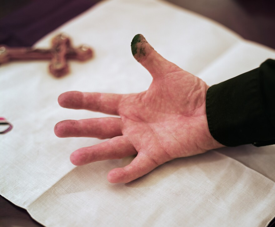 The thumb of the Rev. Patrick Conroy, chaplain of the U.S. House of Representatives, is stained from ashes he made this year for Ash Wednesday.