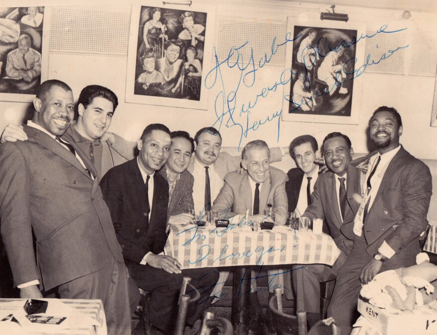 "Gabe Baltazar (fourth from left) at New York City's Birdland Club in 1962, with members of Stan Kenton's band and the Count Basie Orchestra. The photo, from Baltazar's collection, is signed by Kenton (fourth from from right) and trumpeter Harry ""Sweets"" Edison (second from right)."