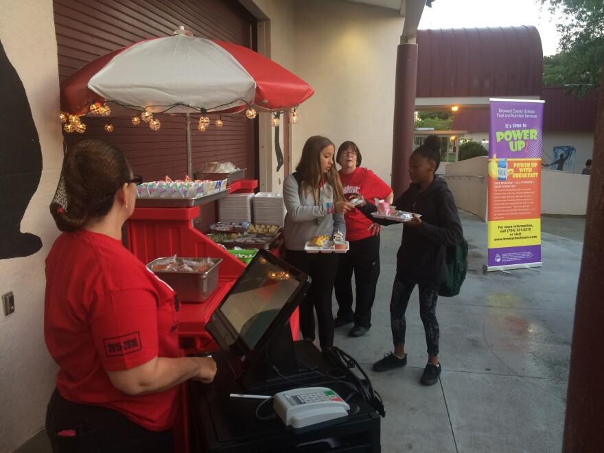 """Students at Deerfield Beach Middle School get breakfast at the school's outdoor """"Grab N Go"""" kiosk."""