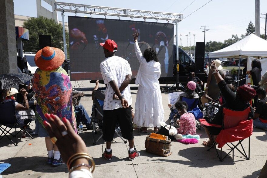 Fans of soul music icon Aretha Franklin watch the singer's funeral on a giant screen outside Greater Grace Temple.