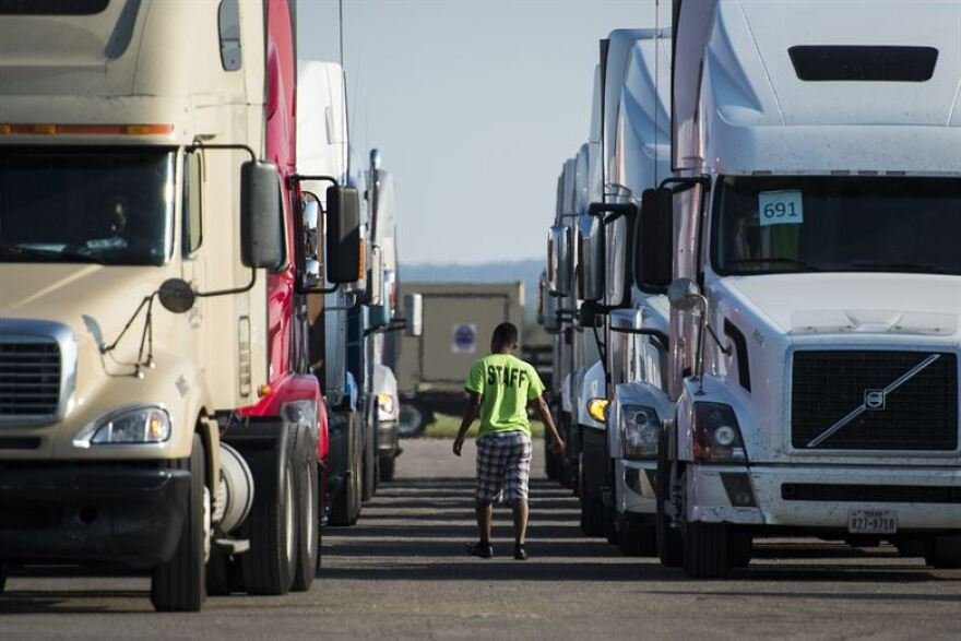 Two lines of forward-facing trucks with a man walking away between them.