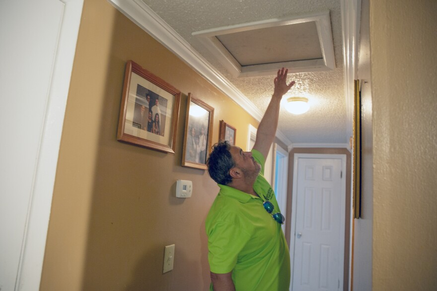 A middle aged man in a green polo shirt points to the air ducts and crawl spaces in a family home where mold is suspected.