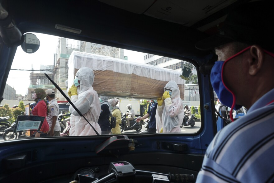 Officials from the Cilandak Subdistrict Office and Police Department carry a coffin in the streets of Jakarta, Indonesia, as part of a campaign to scare people into following pandemic guidelines.