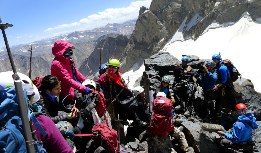 """The girls who made the """"Lion Daughters"""" summit take a rest at the top as a video crew from HBO/Vice films them."""