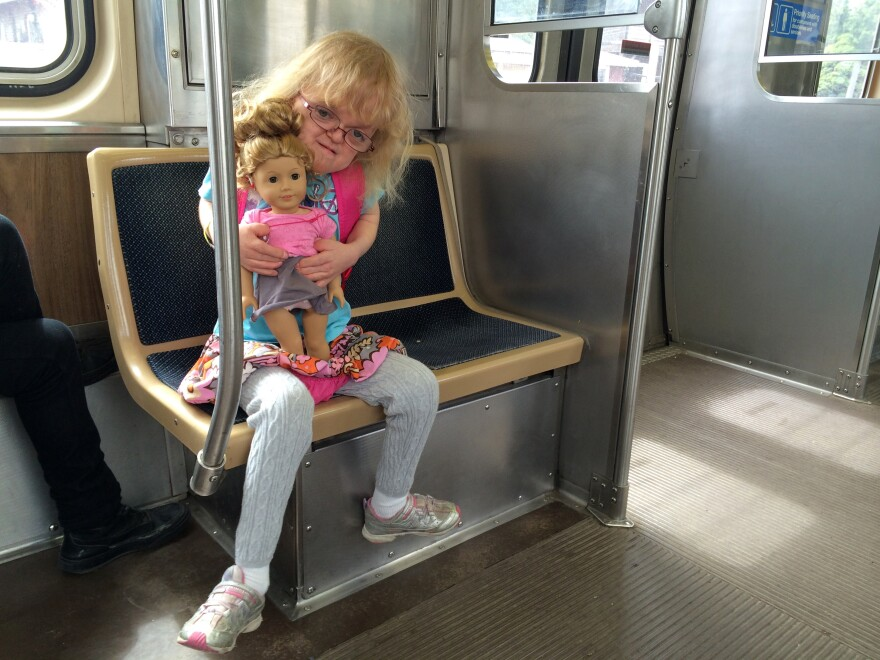 """Dominika Tamley and her doll """"Isebelle"""" ride the train together in Chicago. Like Dominika, Isebelle has a hearing aid. """"She's like a mini-me,"""" Dominika says."""