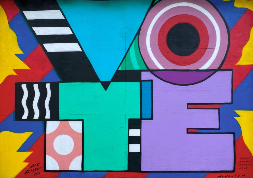 A colorful mural with big block letters that spell the word vote