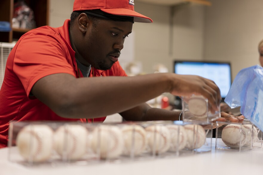 Kenneth Harris works in the Authentics Shop and helps package the baseballs for sale on Aug 16.