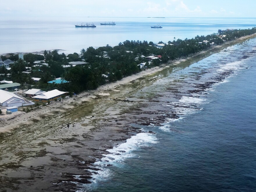 The ocean (right) and the lagoon (left) are separated by a thin strip of land in Funafuti, Tuvalu. The small South Pacific island nation is striving to mitigate the effects of climate change. Tuvalu's 11,000 inhabitants see effects such as rising sea levels in their daily life.