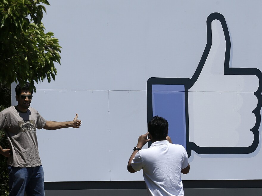 A man poses for photos in front of a sign at the entrance to the Facebook campus in Menlo Park, Calif., on Friday.
