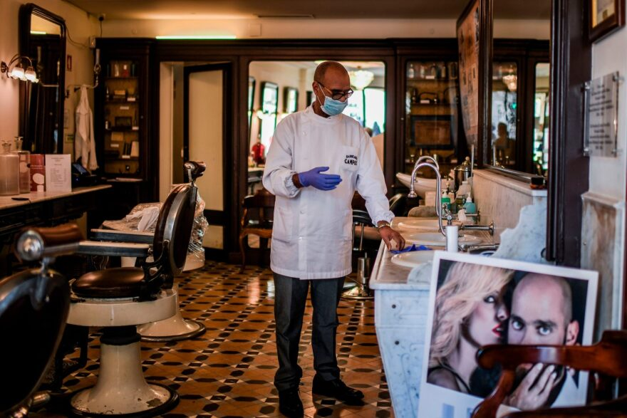 Portuguese barber Elizio da Silva Gomes wearing a protective mask puts on his gloves at the Campos barbershop in Lisbon.