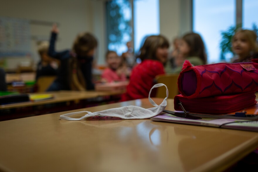 A mask sits on a desk at a primary school in Weimar, Germany. Students are required to wear masks in the hallways and on the playground but not while sitting in class. If coronavirus cases increase in the community or are found in the school, then tighter restrictions are implemented.