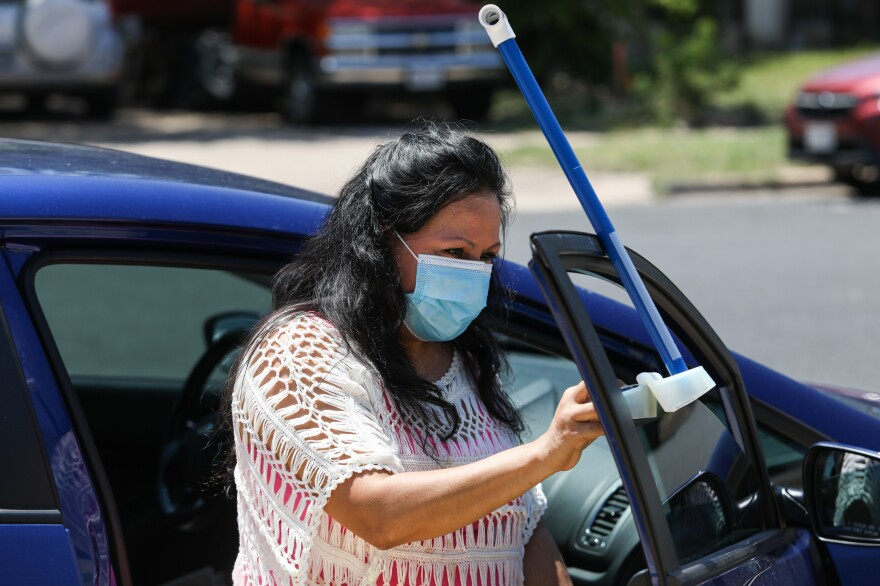 Volunteer Frances Acuña practices attaching a specialized sensor to her car door. It will measure both temperature and humidity.