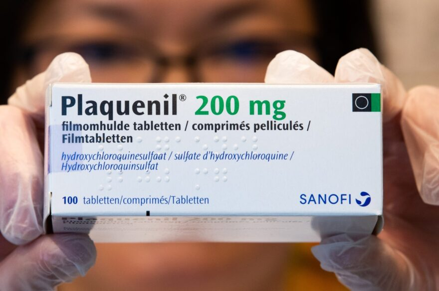Illustration picture shows a pharmacist holding a box of Plaquenil.
