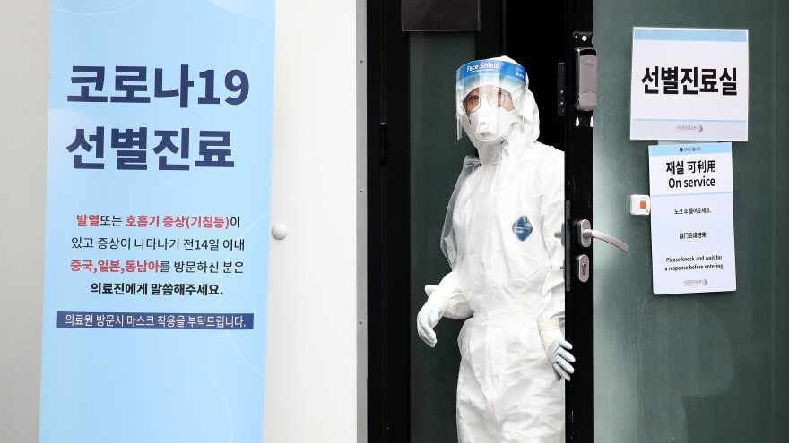 A medical worker takes a look outside a preliminary testing facility at the National Medical Center in Seoul, South Korea, where people suspected of having contracted the novel strain of coronavirus are being tested.