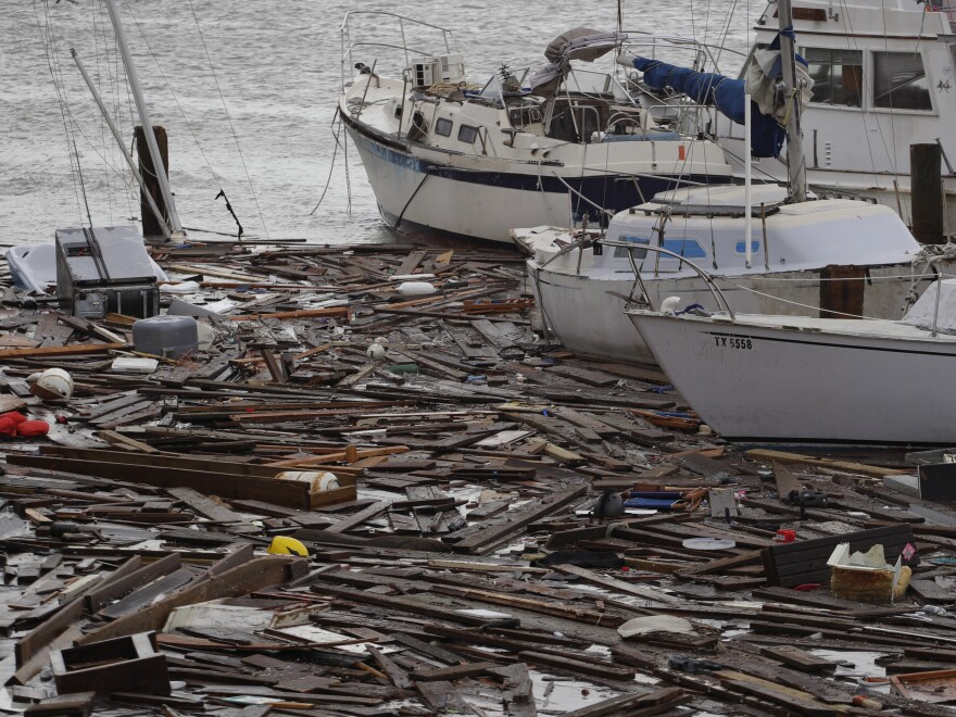 Broken boats and floating debris at a marina in Corpus Christi are among the damage caused by Hurricane Hanna, which was downgraded to a tropical storm and continued to shower Texas with heavy rain on Sunday.
