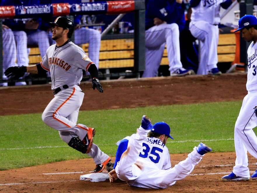 Tucked in the far side of each base is a microphone designed to pick up the scuffle of shoes and gloves. Here, the Royals' Eric Hosmer reaches first base just before the Giants' Gregor Blanco in Game 2 of the World Series.