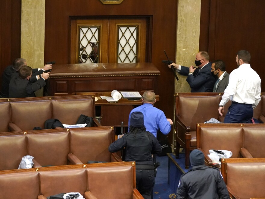 U.S. Capitol police point guns at a door in the House Chamber on January 6.
