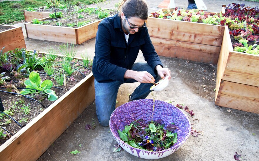 Los Angeles artist Michael Parker pours a dressing of lemon juice, olive oil, salt and pepper over edible flowers, herbs and greens. Parker also made this giant purple porcelain bowl.