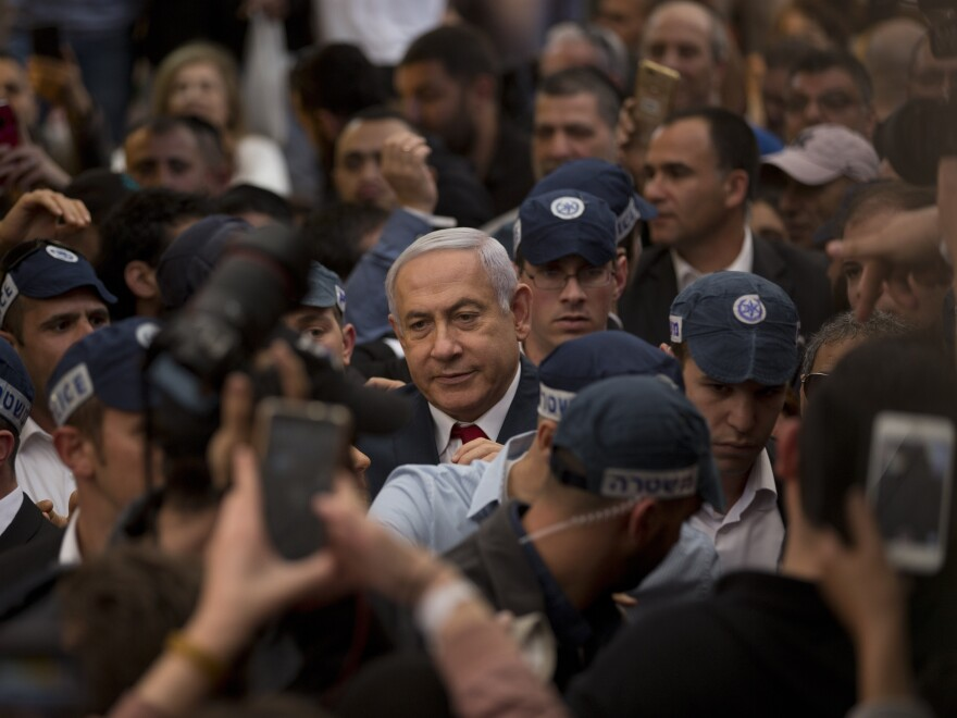 Israeli Prime Minister Benjamin Netanyahu, center, is escorted by security guards during a visit to the Hatikva market in Tel Aviv on Tuesday.