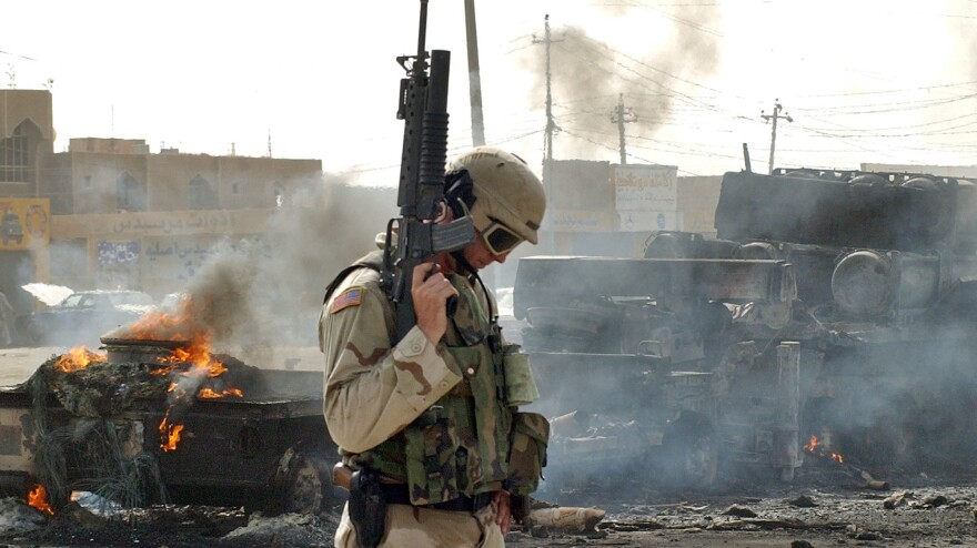 A U.S. Army soldier guards the remains of a burned-out military ammunition truck after it was attacked in Fallujah, Iraq, on Oct. 19, 2003. Fallujah and its surrounds were the site of some of the bloodiest fighting for U.S. troops during the Iraq war.