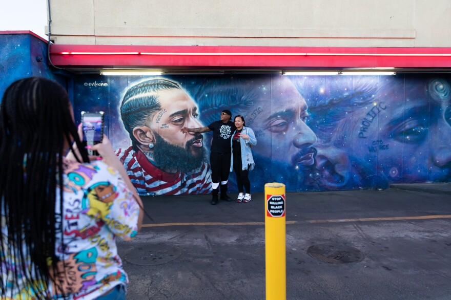 Bria Smith takes pictures of her parents Alexandria and Byron Smith in front of a Nipsey Hussle mural adorning the side of a FatBurger restaurant in Crenshaw. The visitors from Milwaukee got out to take photos while in line for food Dec. 5, 2020.