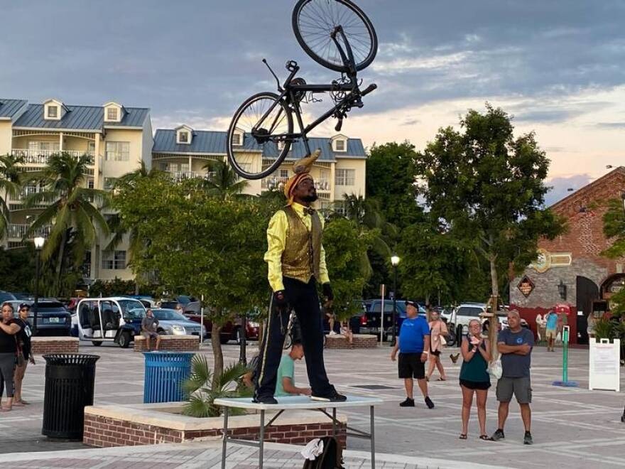 a performer balances a bike on his head at mallory square in key west - site of the nightly sunset celebration